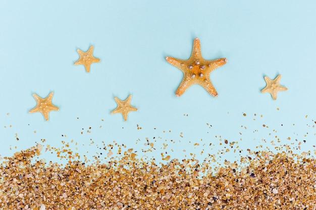 푸른 서머타임 또는 해변 컨셉의 파스텔 색상에 불가사리와 모래가 있는 여름 플랫