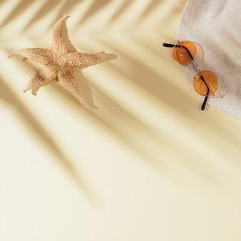 야자수 잎의 그림자와 함께 모래에 태양 모자 색 선글라스 불가사리와 여름 플랫 누워