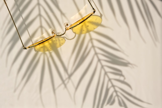 Summer flat lay with yellow sunglasses on water background with shadows of palm leaves and copy space. concept of summer hot day on beach.