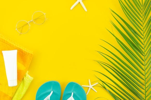 夏フラット横たわっていた黄色の背景。日焼け止めクリーム、スリッパ付きタオル