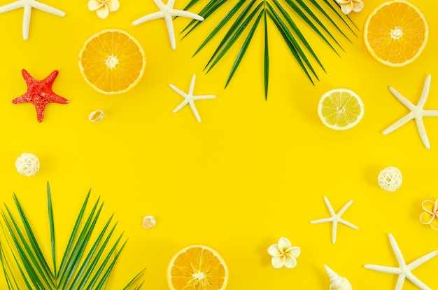 Summer flat lay on yellow background with palm leaf branch, starfishes