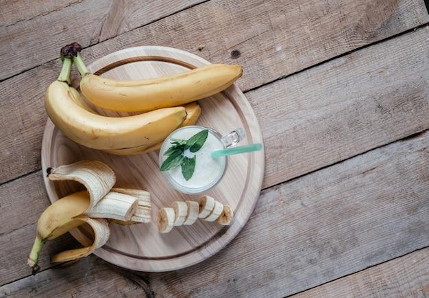 Летний плоский с банановым смузи или молочным коктейлем, листьями мяты и соломой в стакане на темном деревянном столе, летними напитками