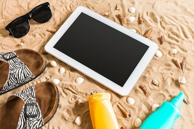 夏のビーチサンダル、タブレット、サングラス、砂の上の貝殻。あなたのテキストのための場所で。上面図