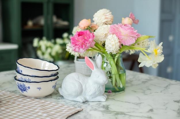 Летние цветы и посуда фарфоровые тарелки на кухонном столе с пасхальным декором