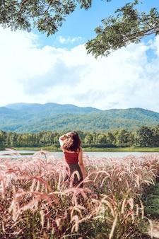 美しい夏の花。牧草地の休暇で夏の太陽を待っている若いアジアの女性素晴らしい自然