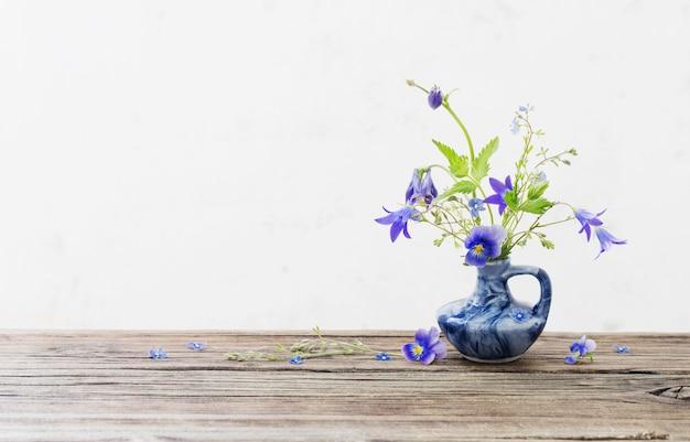 古い木製のテーブルの上の青い水差しの夏の花