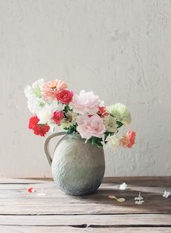 배경 오래 된 흰색 벽에 나무 테이블에 세라믹 주전자에 여름 꽃
