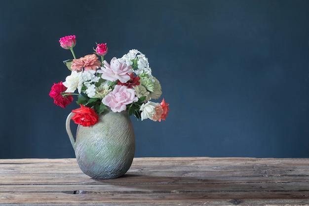파란색 배경에 나무 테이블에 세라믹 주전자에 여름 꽃
