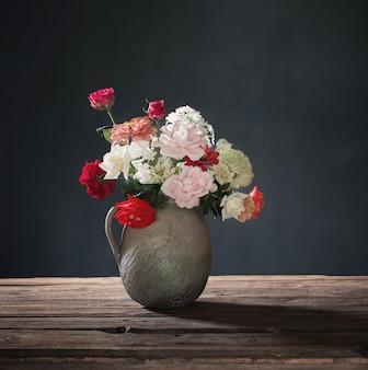 어두운 배경에 있는 나무 테이블에 있는 세라믹 주전자에 있는 여름 꽃