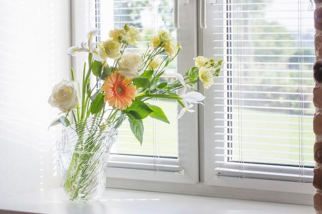 Windowsiilのガラスの花瓶の夏の花