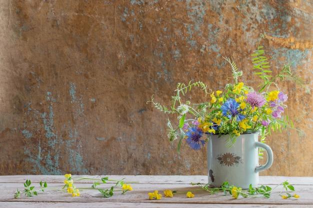 Летние цветы в старой чашке на деревянном фоне