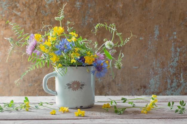 Летние цветы в старой чашке на деревянной стене