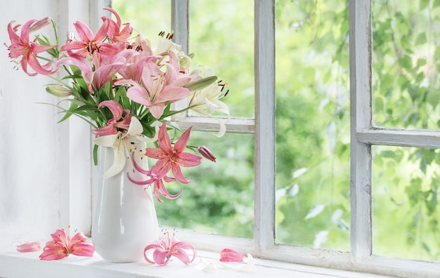Летние цветы в вазе на белом подоконнике