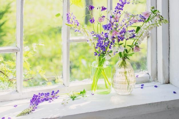 日光の下で窓辺に花瓶の夏の花