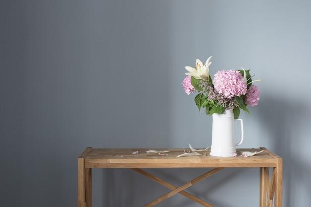 나무 선반에 흰색 주전자에 여름 꽃