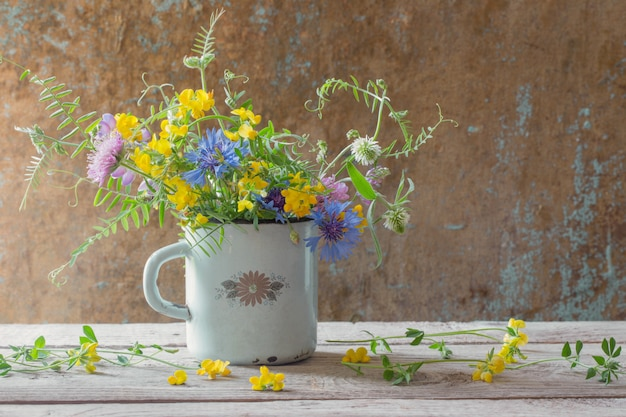 Summer flowers in old cup on wooden wall