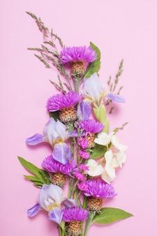 Летние цветы на розовой бумажной поверхности
