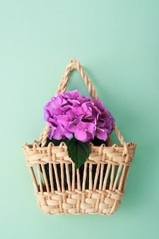Summer flowers in straw basket on turquoise with copy space.