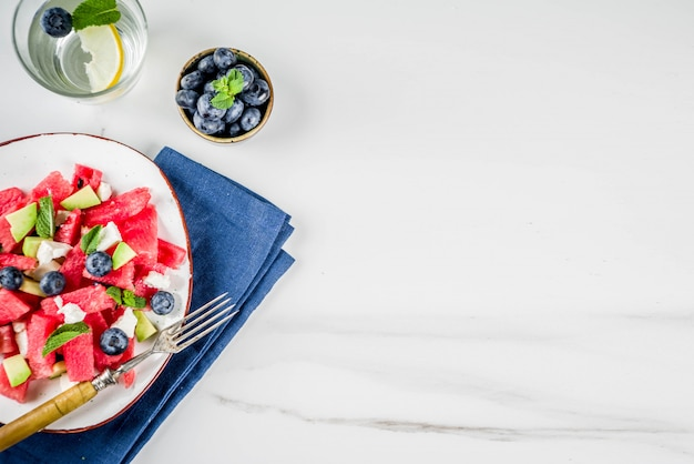 Summer food concept, fresh cold watermelon salad with feta cheese, blueberry, avocado