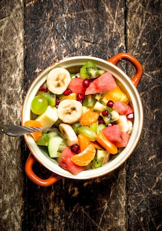 Summer food . fruit salad in a bowl. on wooden background.