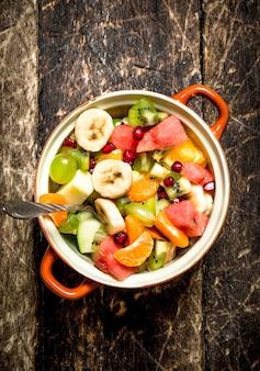 夏の食べ物。ボウルにフルーツサラダ。木製の背景に。