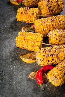 Summer food. ideas for barbecue and grill parties. grilled corn grilled on fire. with a sprinkle of cheese (mexican elotes), hot chili pepper and lemon. on a dark stone table. copy space