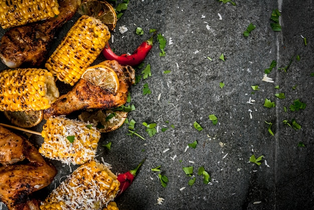 Summer food. ideas for barbecue, grill party. corn and chicken (legs, wings) grilled, fried on fire. with a sprinkle of cheese (elotes), hot chili pepper, lemon. dark stone table. copy space top view
