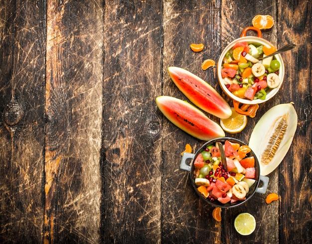 夏の食べ物。トロピカルフルーツのサラダ。木製の背景に。