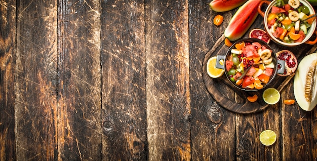 Summer food salad of tropical fruits on wooden background