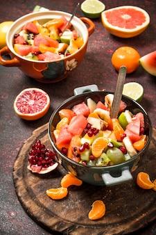 夏の食べ物。エキゾチックなフルーツのトロピカルサラダ。素朴な背景に。