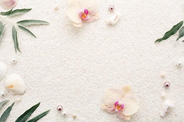 白い砂浜に貝殻、花、真珠の夏のフレーム。パステル背景、コピースペース。スパリラクゼーション。