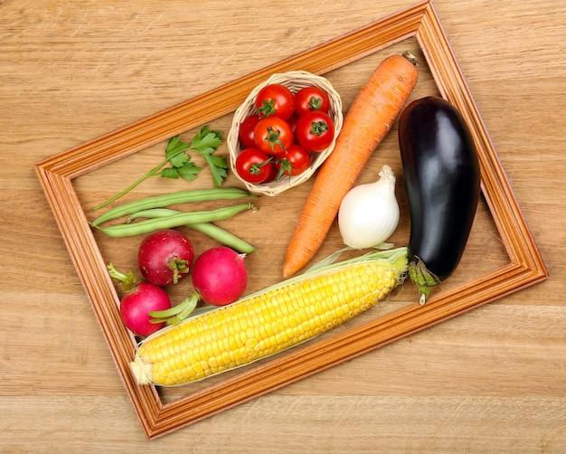 木製の新鮮な有機野菜や果物と夏のフレーム