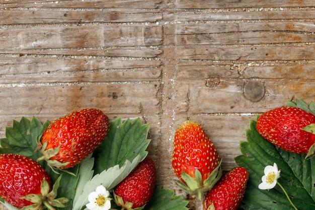 빈티지 나무 배경에 큰 익은 정원 딸기가 있는 여름 프레임