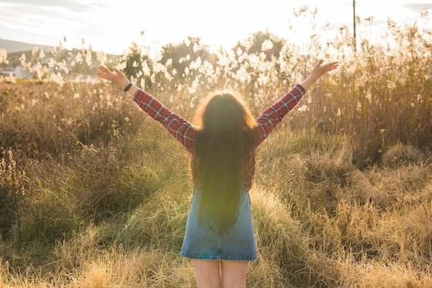 夏の自由と休日の概念幸せな女性は金色の小麦の背面図で腕を上げた