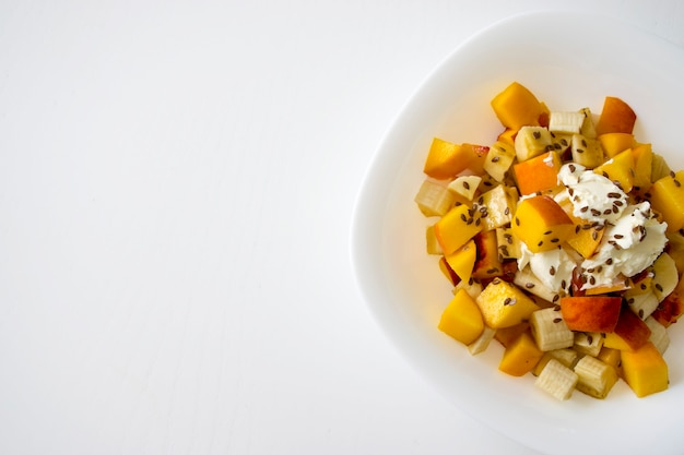 白いボウルに柔らかいチーズと亜麻の種子を添えたカラフルなフルーツサラダと夏の新鮮なボウル。低カロリーのデザート。天然有機食品。おいしいヘルシースナック、軽くてシンプルなランチ。