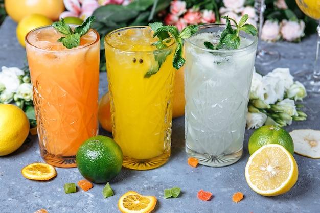 Летние свежие прохладительные напитки ледяной лимонад в кувшине и лимоны и апельсин с мятой на столе на открытом воздухе апельсиновый лимонад в стакане