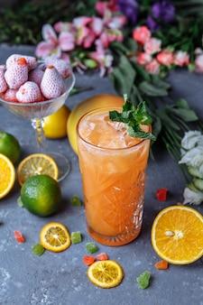 Летом свежие прохладительные напитки. ледяной лимонад в кувшине и лимоны и апельсин с мятой на столе открытый. апельсиновый лимонад в стакане