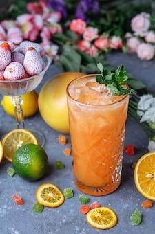 Летние свежие прохладительные напитки. ледяной лимонад в кувшине и лимоны и апельсин с мятой на столе на открытом воздухе. апельсиновый лимонад в стакане.