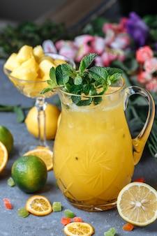 Летние свежие прохладительные напитки. ледяной лимонад в кувшине и лимоны и апельсин с мятой на столе на открытом воздухе.