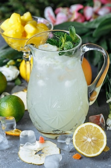 Summer fresh cold drink beverages. ice lemonade in the jug and lemons and orange with mint on the table outdoor.
