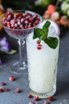 夏の新鮮な冷たい飲み物。屋外のテーブルにクランベリーとミントで飾られたレモンとアイスレモネード。ガラスのレモネード。