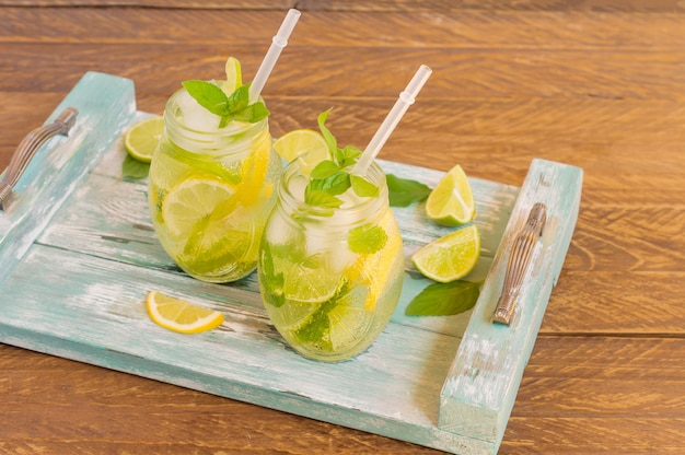 Летний свежий холодный лимонад с лаймом, лимоном, мятой и льдом подается на синем деревянном подносе. безалкогольный напиток.