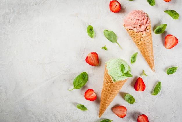 夏の新鮮なデザート。コーンの緑のバジルと赤いストロベリーアイスクリーム。バジルの葉と新鮮なイチゴの周りの白い石のテーブルの上。白い石のテーブルの上。トップビューコピースペース