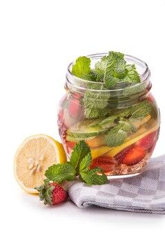 Летний свежий фруктовый ароматизированный настой воды из лайма, огурца, клубники и мяты, изолированных на белом фоне