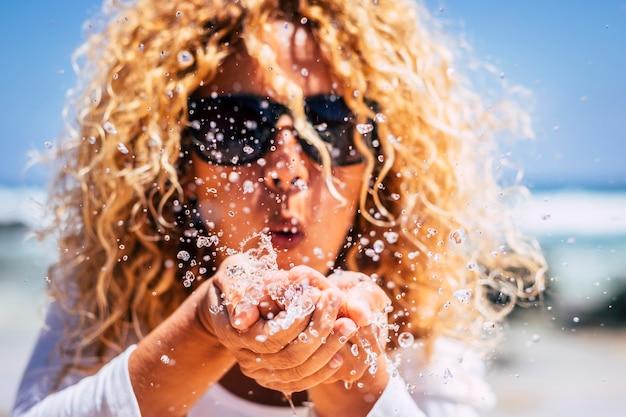 手から水を吹く金髪の巻き毛の美しい若い女性と夏の新鮮な休日の休暇のコンセプト-太陽の下で白人の人々を楽しんで遊ぶ-水滴を閉じる-海と海の自然