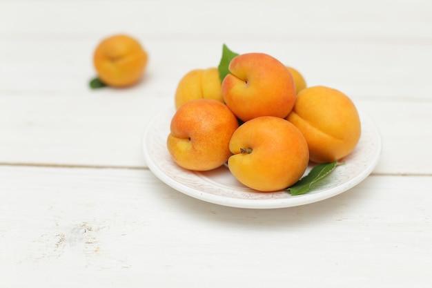 Летние фрукты - абрикосы, белый деревянный фон
