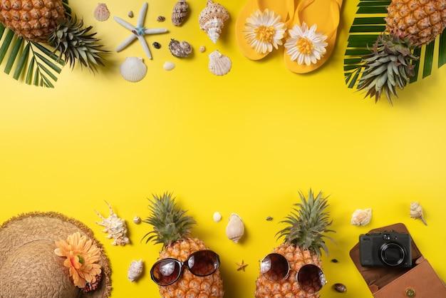 夏の果物の背景デザインコンセプト。黄色の背景に貝殻、パイナップル、ヤシの葉と休日の旅行ビーチの上面図。