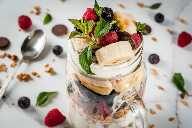 Summer fruit berry breakfast. healthy banana split breakfast with cream cheese, raspberries, blackberries, mint, white and pink chocolate. in mason jar, marble table.