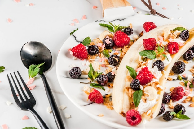 Summer fruit berry breakfast. healthy banana split breakfast with cream cheese, raspberries, blackberries, mint, white and pink chocolate. on white marble plate, marble table.