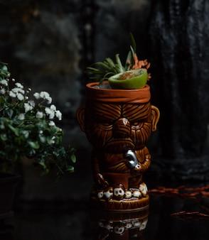 Летний фруктовый коктейль с кусочками внутри этнической чашки